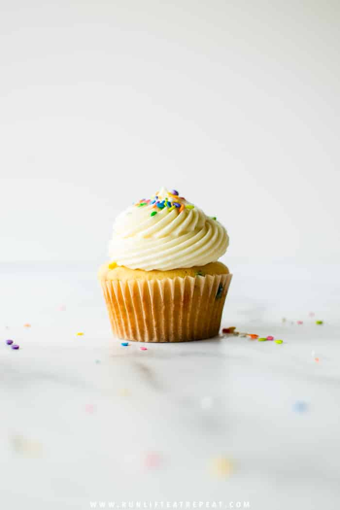 These are the softest and fluffiest vanilla cupcakes studded with rainbow sprinkles. Perfect for a birthday celebration! Find the recipe at runlifteatrepeat.com.