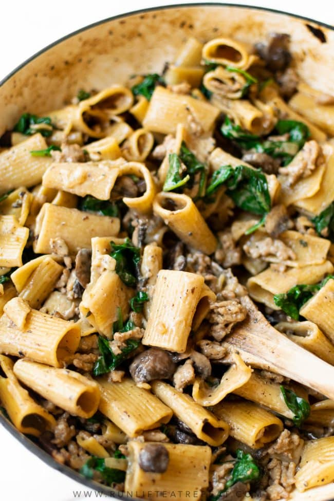 This creamy Italian sausage pasta is coated in a light, garlic, cheesy cream sauce and filled with Italian sausage, mushrooms and spinach. It's the one pan recipe that will be your new favorite weeknight dinner.