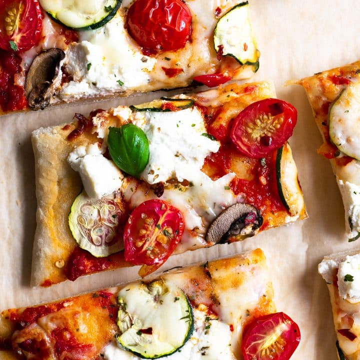 This zucchini & tomato herbed ricotta flatbread pizza uses my favorite flatbread dough recipe. It's topped with herbed garlic ricotta cheese, zucchini, tomatoes, and a little fresh basil to finish it off. It's a dinner recipe that the entire family loves!